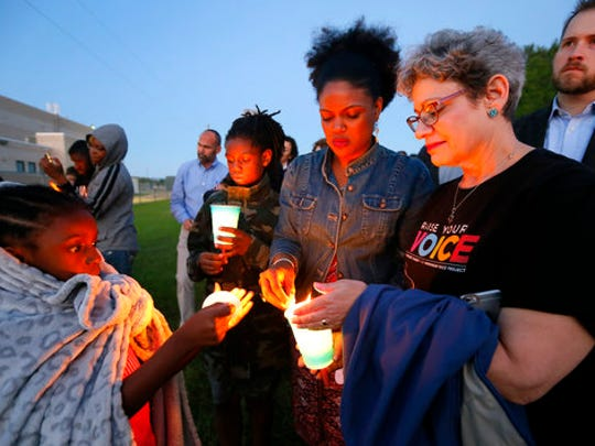 Hope Waters, left, her brother Jeremiah, center rear, and their mother Yulise, center right, light candles with Linda Abrasion Evans, right, during a candle light vigil for Jordan Edwards in Balch Springs, Texas, Thursday, May 4, 2017. The prosecutor's office investigating the death of a black teenager who was shot by a Dallas-area police officer had once filed a complaint over that officer's aggressive behavior, according to records obtained Thursday by The Associated Press.
