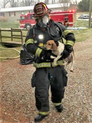 Lt. Shane Barkley of the New Concord Fire Department carries the momma dog to safety after being rescued from a burning barn.
