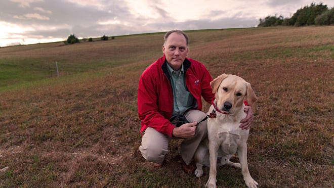"""Dante Capriotti sits next to his family's yellow lab, Romeo, in the backyard of their home in Fishersville where the two were attacked by three off-leash dogs last Sunday. """"It was exhausting,"""" said Capriotti, who tried to wrestle the other dogs off his pet for roughly 10 minutes before shooting one of them to break up the scuffle."""