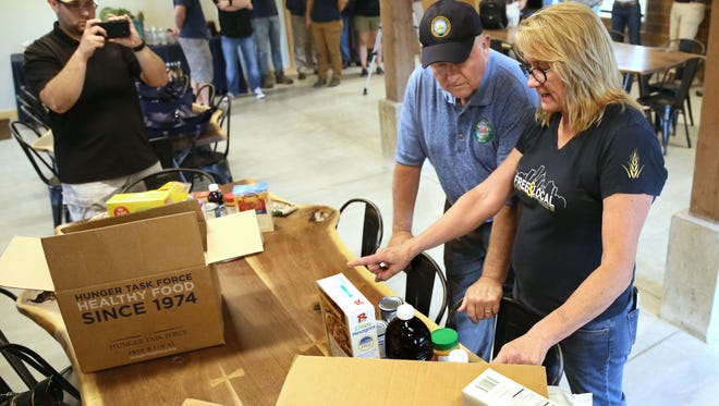 United States Agriculture Secretary Sonny Perdue toured the Hunger Task Force farm in Franklin in 2017. Sherrie Tussler, executive director of Hunger Task Force (right), explains to Perdue how they pack food boxes for families and seniors who utilize some of the USDA  commodity food.