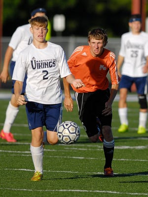 Marysville's Trevor Roeske attacks with Marine City's Billy Welser in close pursuit in their soccer match Monday evening. The Vikings cruised to an 8-0 win.
