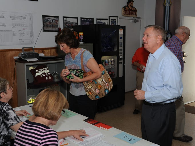 Poll worker Joann Sanders checks in Lindsey Graham, who prepares to vote in the 2014 South Carolina Primary election Tuesday, June 10.