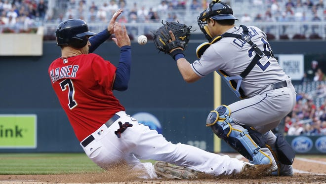 The Minnesota Twins' Joe Mauer slides in to score on a single by Trevor Plouffe as he beat the tag by Tampa Bay Rays catcher Hank Conger in the third inning Friday in Minneapolis.