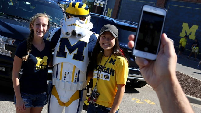 Wolverines Trooper Jon Leopold of Goodrich was a popular Stormtrooper during tailgating in the Michigan Stadium parking lot. He is photographed with Erin Evans and Rylee Kim, both from Dexter.