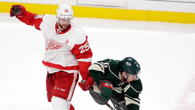 Minnesota Wild left wing Zach Parise becomes entangled with Detroit Red Wings defenseman Mike Green as he plays the puck during the third period Sunday, Feb. 12, 2017, in St. Paul, Minn.