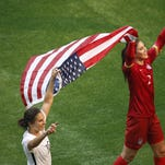 United States midfielder Carli Lloyd (10) and United States goalkeeper Hope Solo (1) celebrate with an American flag after defeating Japan in the final of the FIFA 2015 Women's World Cup at BC Place Stadium. United States won 5-2. Mandatory Credit: Erich Schlegel-USA TODAY Sports