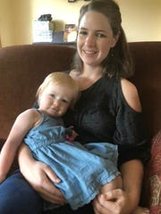 Amy Marchant, with her daughter Autumn, at home in Brighton. Marchant settled a lawsuit with The Naz - Brighton's Nazarene Church, earlier this month. She was criticized in 2018 by a church staff member while breastfeeding inside the church.
