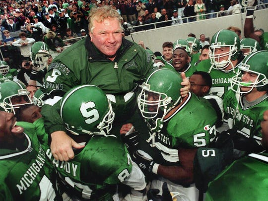 Former MSU head football coach George Perles is carried off the field after his last game as coach at Spartan Stadium by his team after their come-from-behind victory over Iowa in November 1994.