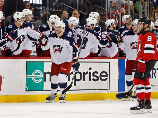 Columbus Blue Jackets defenseman Scott Harrington (4) celebrates his goal with teammates in front of New Jersey Devils defenseman Will Butcher (8) during the second period of an NHL hockey game, Tuesday, Feb. 20, 2018, in Newark, N.J.