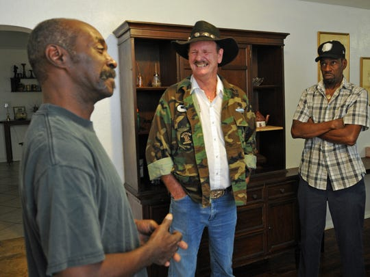 George Taylor, Sr., center, president and founder of National Veterans Homeless Support, talks with Army veteran George Gore, left, and Adiel Brooks, a Marine Corps veteran. They are in a renovated Titusville home for veterans in need.