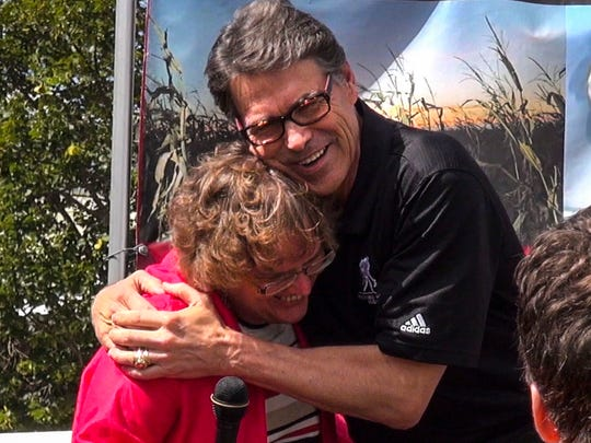 """Texas Gov. Rick Perry hugs Register executive news director Carol Hunter after she thanked him for speaking at the Soapbox on Tuesday. Perry responded: """"You're welcome. I'm awesome!"""""""