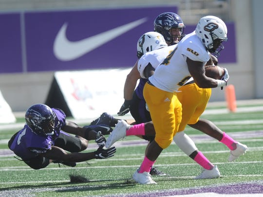 ACU's Royce Moore, left, can't hold onto Southeastern Louisiana running back Darren Johnson on a play in the first quarter. The Lions beat ACU 56-21 in a Southland Conference game Saturday, Oct. 21, 2017 at Wildcat Stadium.