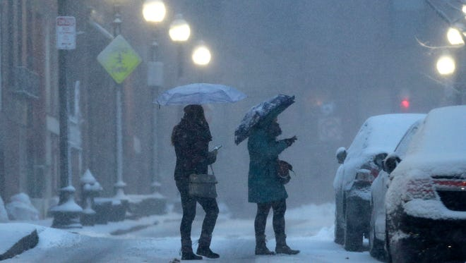 People use umbrellas to protect themselves from falling snow as they cross a street in Boston's North End neighborhood. Boston broke an all-time snowfall record on Sunday.