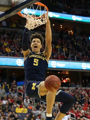 Michigan forward D.J. Wilson (5) dunks the ball against Wisconsin on March 12, 2017.