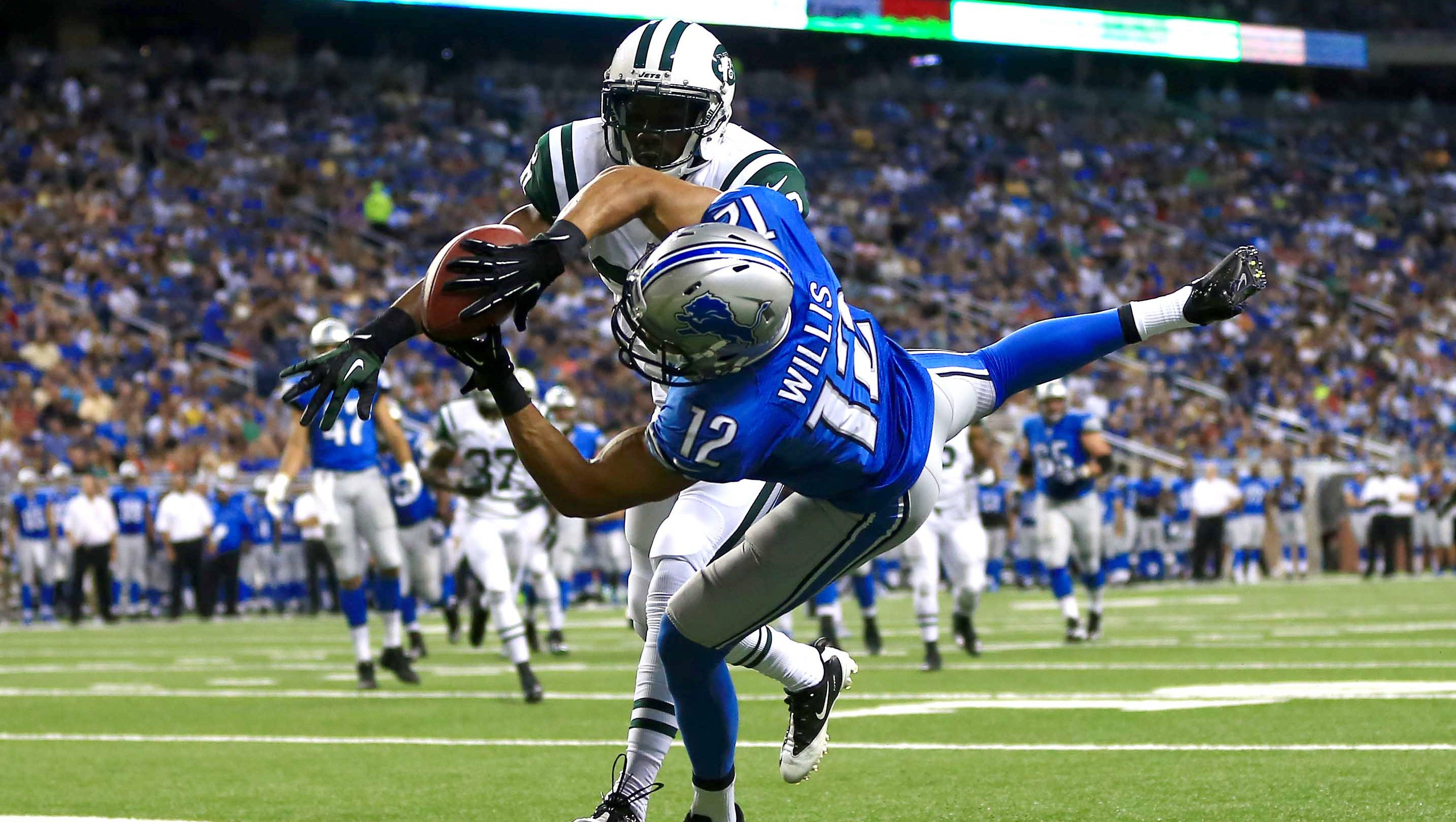 Detroit Lions wide receiver Matt Willis (12) catches a pass in the end zone for a touchdown while being defended by New York Jets running back Chad Spann (30) in the second quarter of a preseason game at Ford Field.