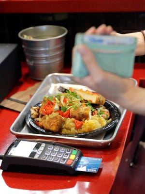 A customers uses a credit card machine to pay for food at Peli Peli Kitchen in Houston. Owner Thomas Nguyen had a change of heart after transitioning one of his three Peli Peli South African fine dining restaurants and his Peli Peli Kitchen fast casual location to a no-cash policy.