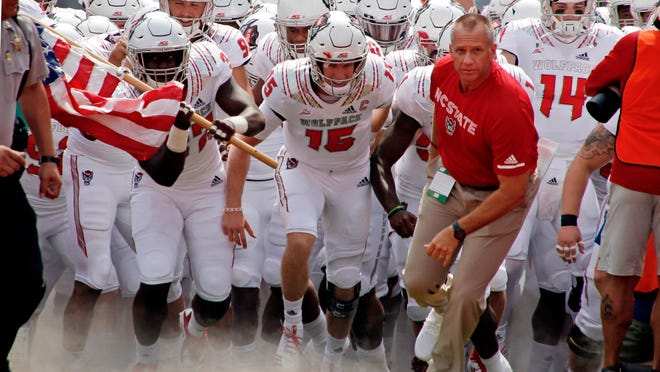 FILE - In this Saturday, Sept. 8, 2018, file photo, North Carolina State head coach Dave Doeren leads the team onto the field for an NCAA college football game against Georgia State in Raleigh, N.C. Doeren and the Wolfpack face Virginia on Saturday. (AP Photo/Chris Seward, File)