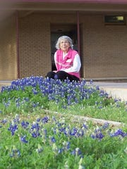 Mrs. Howell sits on the sidewalk leading to her classroom
