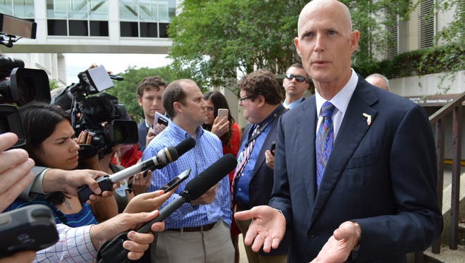 Gov. Rick Scott talks with Capitol reporters before leaving for Washington on Tuesday.