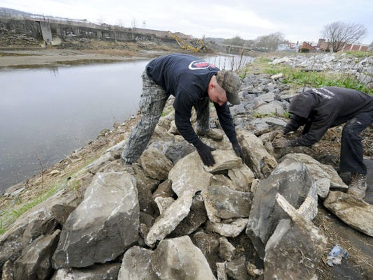 Nick Sellers, left, and Brent Burdett with Asher Construction help place large stones, known as riprap, along the Codorus Creek to help prevent runoff. The company is among those working on channel maintenance for flood control underway in two projects.