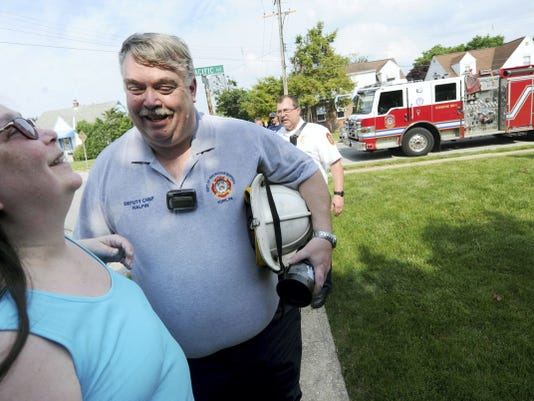 Greg Halpin jokes with his wife, Louann, after arriving to his York home in a fire truck Thursday. Halpin retired as deputy chief of the city's Department of Fire and Rescue Services, effective Tuesday. The 34-year department veteran was surprised with the ride home where fellow firefighters, family and friends greeted him to celebrate.