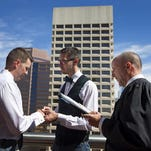 Phoenix Municipal Court Judge Kevin Kane marries same-sex couple Tim Palak,44, left, and Jason Bannecker, 39, of Phoenix, on a Phoenix City Hall balcony. October 17, 2014.
