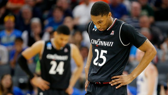 Cincinnati Bearcats guard Kevin Johnson (25) and Cincinnati Bearcats forward Kyle Washington (24), background, rest their hands on their hips in the final moments of the 79-67 loss to UCLA.
