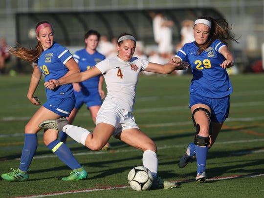 Arlington's Michaela Fasolino fires off a shot in front