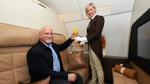 Gino Bertuccio, the first passenger to travel in Etihad's three-room Residence suite, is served by butler Georgina Henderson.