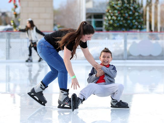 Daisy Taylor tries to keep her brother, Kaleb Taylor, from falling onto the melting ice at the Promenade Ice Pond at the Fountains at Farah Monday. Warmer-than-normal temperatures caused the ice to melt slightly, but didn't deter El Pasoans from enjoying some winter fun under the sun.