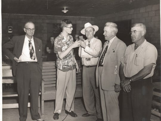 A young John Hood, second from left, interviews people