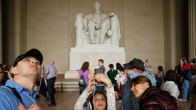 In this Tuesday, April 7, 2015 photo, Asal Amrieva of New York, N.Y., center, takes a photograph while visiting the Lincoln Memorial in Washington. A century and a half after Lincoln was killed, people continue to connect with him in almost personal terms, while searching anew for his relevance to the Republic he left behind. (AP Photo/Andrew Harnik)