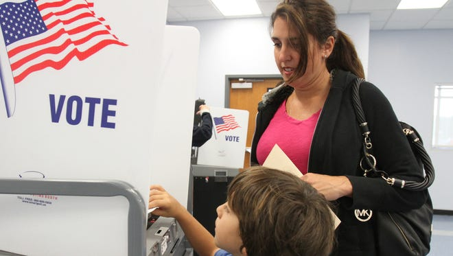 A son helps his mom post her ballot during a past year's school budget vote.