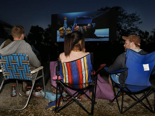 """From left: Andrew Schnee of Colerain Township, Kayla Meyer of West Chester, and Kent Johnson of Hamilton sit out in their lawn chairs as they watch """"Despicable Me 2"""" in Hanover Township."""