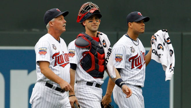 Minnesota Twins pitching coach Rick Anderson, left,  catcher Eric Fryer, center, and starting pitcher Yohan Pino, right, walk to the dugout before a baseball game against the Chicago White Sox in Minneapolis.