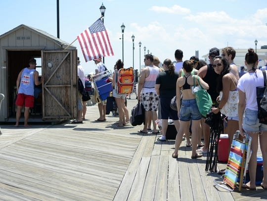 Beach patrons wait in line for admission to the beach