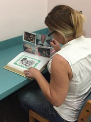 Laura Youngblood looking through her scrapbook.