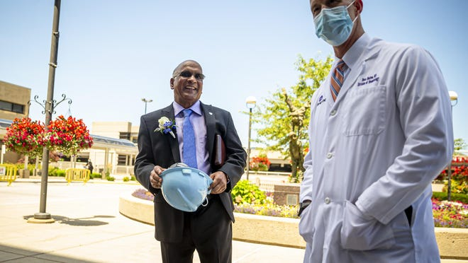 Dr. Babu Prasad, center, retired anesthesiologist, is given a hard hat by Dr. Beau Batton, right, director of newborn services, HSHS St. John's Children's Hospital NICU, after a press conferencing announcing a donation from Prasad of $1,000,000 to the HSHS St. John's Foundation for the St. John's Children's Hospital NICU project at HSHS St. John's Children's Hospital, Thursday, July 23, 2020, in Springfield, Ill.