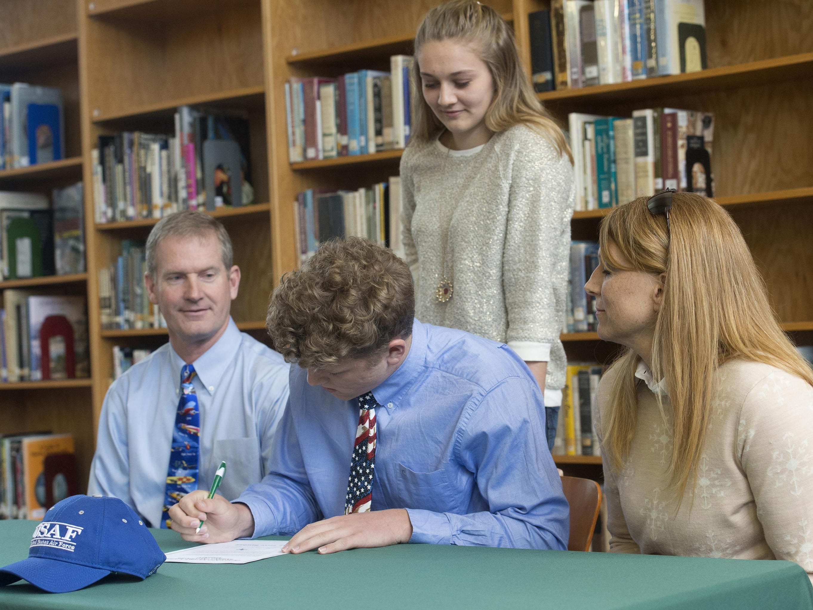 Catholic High School student, Evan Floyd, center, signs with United States Air Force Academy during a ceremony at the school Monday morning, while his family looks on.