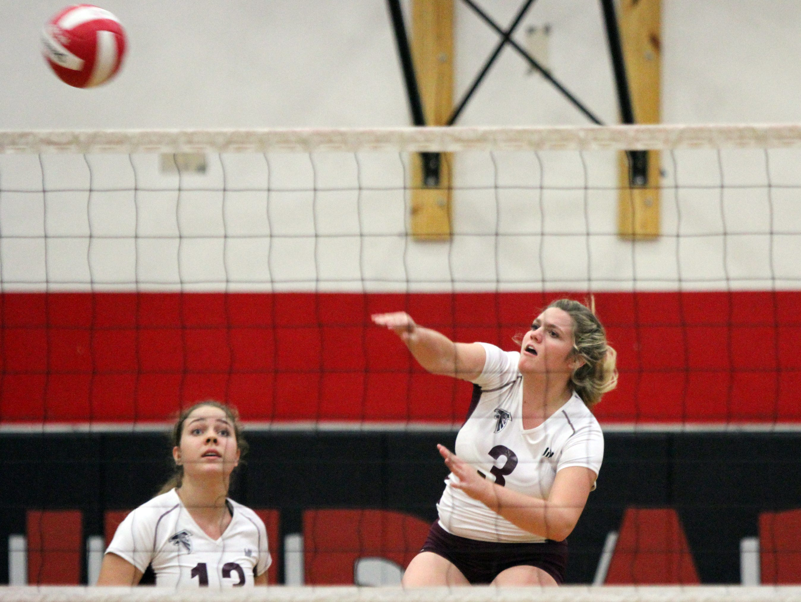 La Quinta's Jolie Samuelson spikes the ball as Camryne Sommaripa looks on during their match against Palm Springs High in Palm Springs on Tuesday.