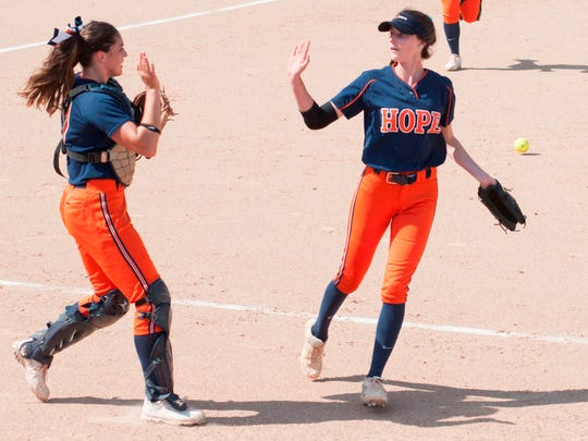 Hope College pitcher Sydney Jones (right) gives catcher Hayley Riestma a high-five.