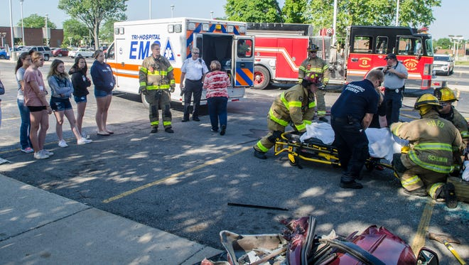 Students watch the mock accident scene Friday morning, June 24, 2016 at St. Clair County Community College.