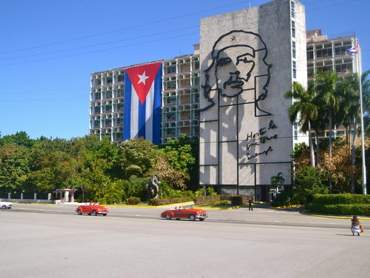 The Cuban flag hangs from a building with a visual of Che Guevara while 1950s cars pass by.