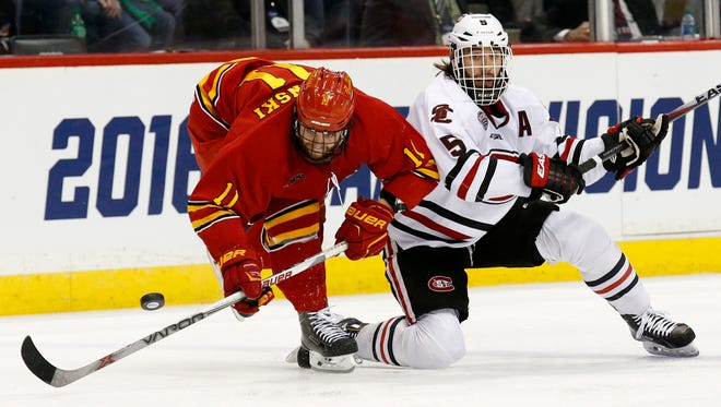 Ferris State center Kenny Babinski (11) and St. Cloud State defenseman Nathan Widman (5) battle for the puck during the second period of an NCAA men's hockey West Regional semifinal in St. Paul, Minn., Saturday, March 26, 2016.