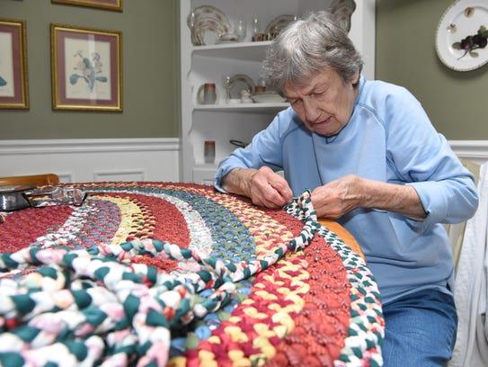 Janice Helmer, 87, works on finishing a braided rug