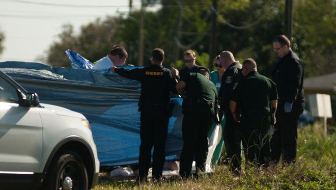 Law enforcement officials assist medical exminer's office at the scene of a vehicle pulled from a canal in Lehigh Acres. At least one body was removed from the SUV.