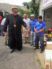 Cardinal Timothy Dolan inspects the chair built for