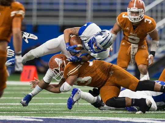 Alice's Roberto Montalvo tackles a Austin McCallum rusher during their Class 5A Division II regional semifinal game Saturday, Dec. 2, 2017, at the Alamodome in San Antonio.