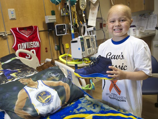 Brody Stephens, 7, poses by his Golden State-themed
