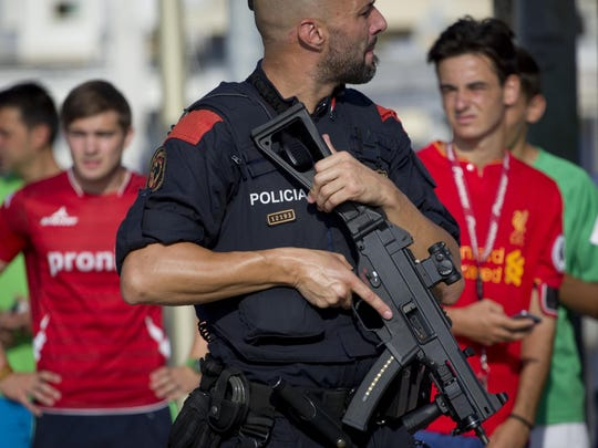 An armed policeman grimaces while on patrol in Cambrils, Spain, Aug. 18, 2017.